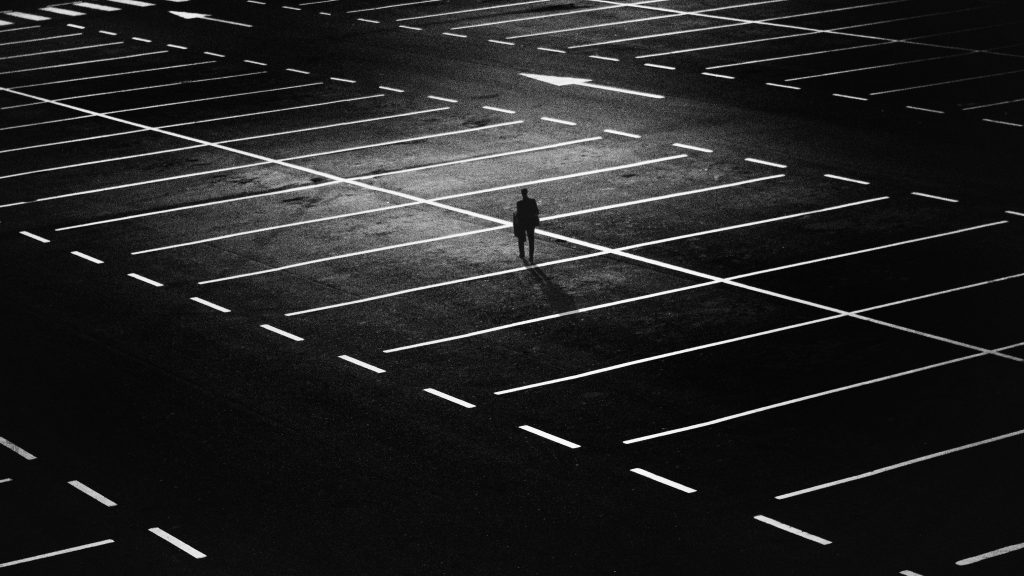man-standing-on-parking-lot-163772-1024x576